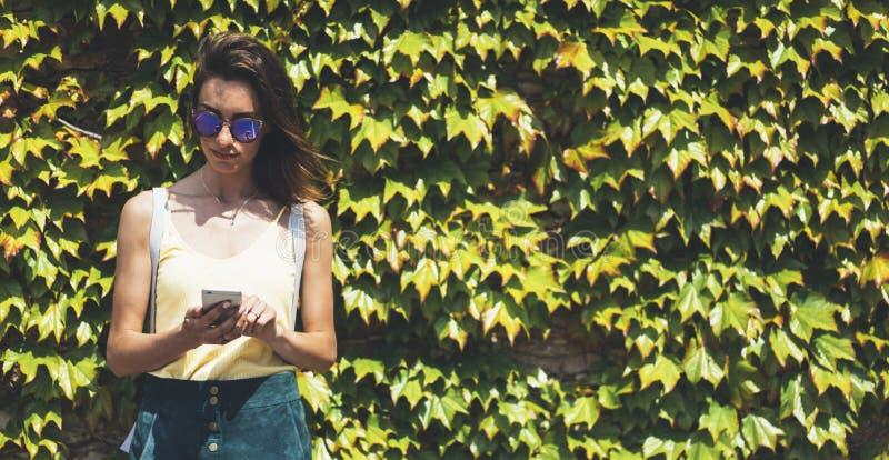 Молодые женщины портрета в солнечных очках используя умный телефон изолированный на насмешке стены природы предпосылки зеленой вв стоковое фото rf