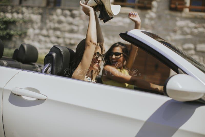 Молодые женщины с солнечными очками управляя ее обратимым верхним автомобилем на яркий солнечный день стоковые изображения