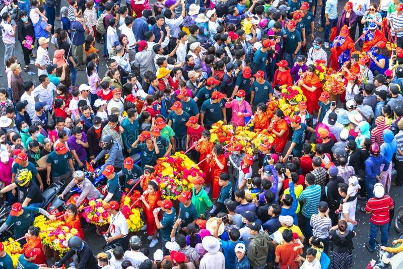 Молодые женщины фонарика фестиваля китайские нося цветки проходят парадом на улице стоковая фотография