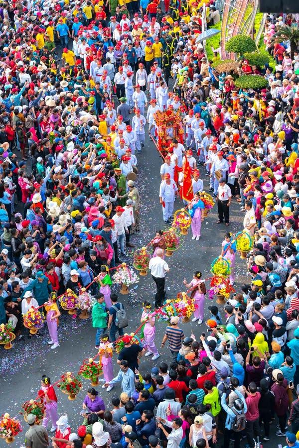 Молодые женщины фонарика фестиваля китайские нося цветки проходят парадом на улице стоковые фотографии rf