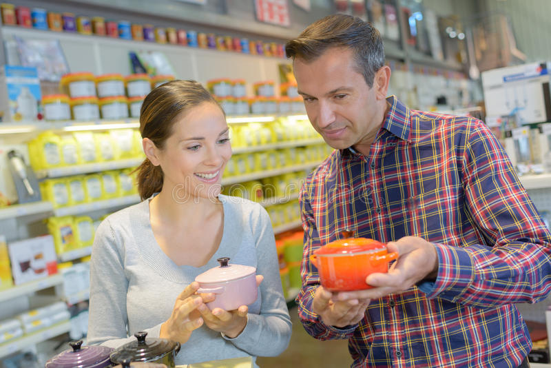 Молодые жизнерадостные пары в разделе cookware на гипермаркете стоковые фото