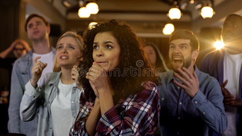 Молодые зрители тревожась о любимой команде, мульти-расовые вентиляторы на стадионе стоковое фото