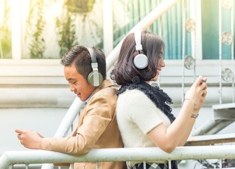 Молодые игры игры мальчика и девушки и слушать музыку на мобильных телефонах стоковое изображение rf