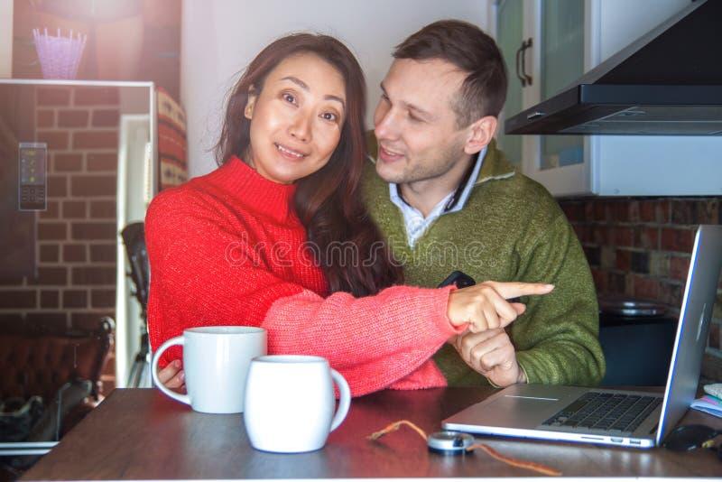 Молодые интересные пары смотря ноутбук дома в кухне и держа смартфон Международная пара на взаимо- стоковая фотография rf