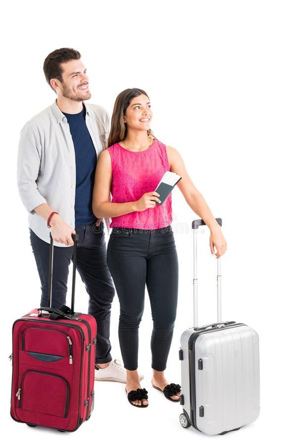 Молодые испанские пары идя на каникулы против белой предпосылки стоковое изображение