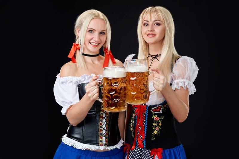 Молодые и красивые баварские девушки с 2 кружками пива на черной предпосылке стоковые фото