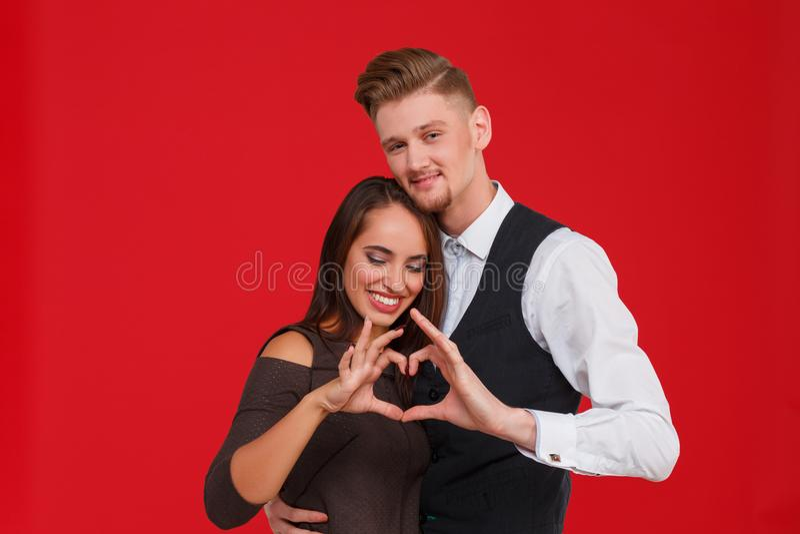 Молодые и красивые пары в влюбленности делают сердце на красной предпосылке Концепция дня ` s валентинки стоковые фотографии rf