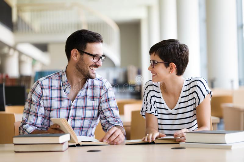 Молодые и красивые студенты изучая в библиотеке стоковое фото rf