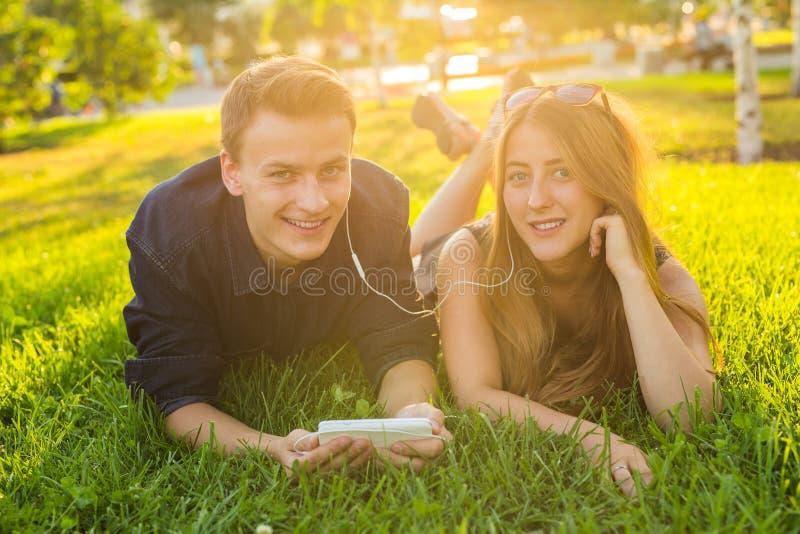 Молодые кавказские симпатичные пары или студенты колледжа лежа вниз на траве совместно, слушающ к музыке Любовь стоковое изображение rf
