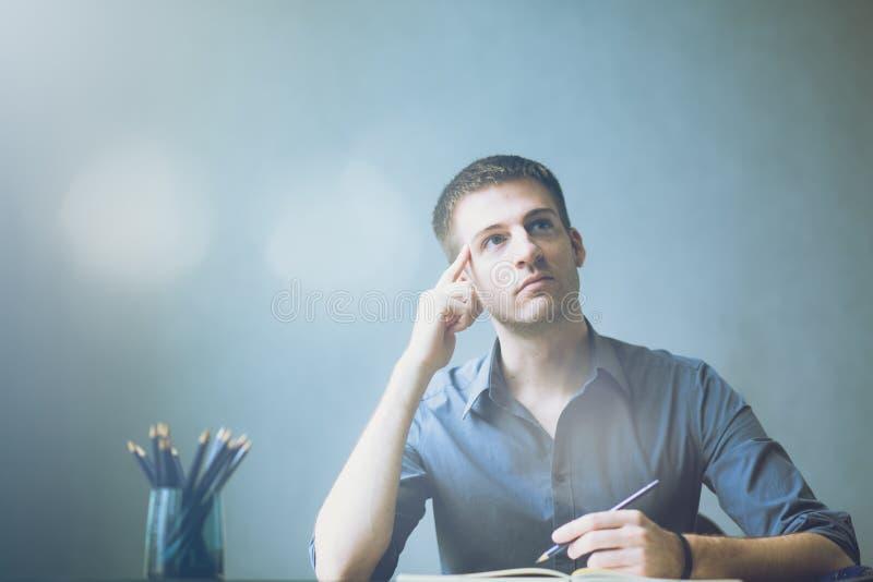 Молодые кавказцы бизнесмена сидя на таблице офиса стола и принимая примечания в тетради Запись и смотреть к правой стороне стоковая фотография