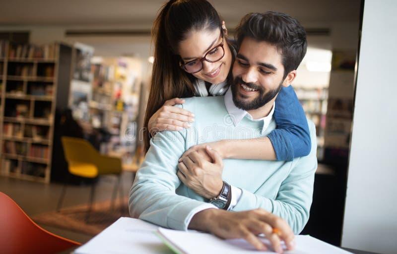 Молодые книги чтения пар и изучать совместно в библиотеке стоковые изображения