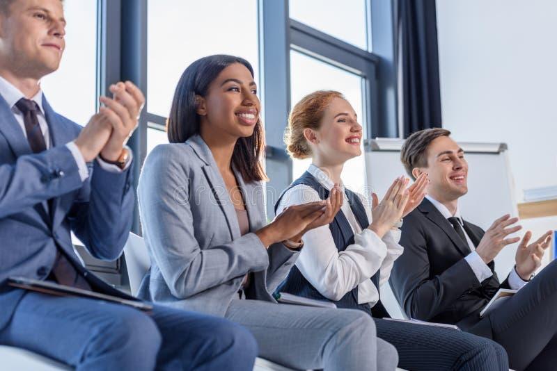 Молодые коллеги аплодируя к представлению стоковое изображение