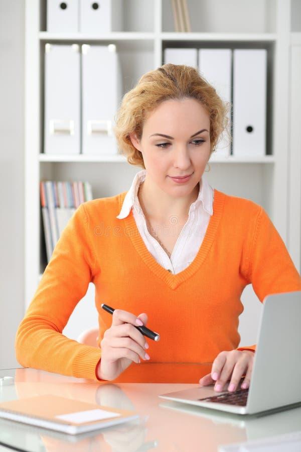 Молодые красивые бизнес-леди или студент связывают портативным компьютером пока сидящ на столе и держащ черноту стоковая фотография