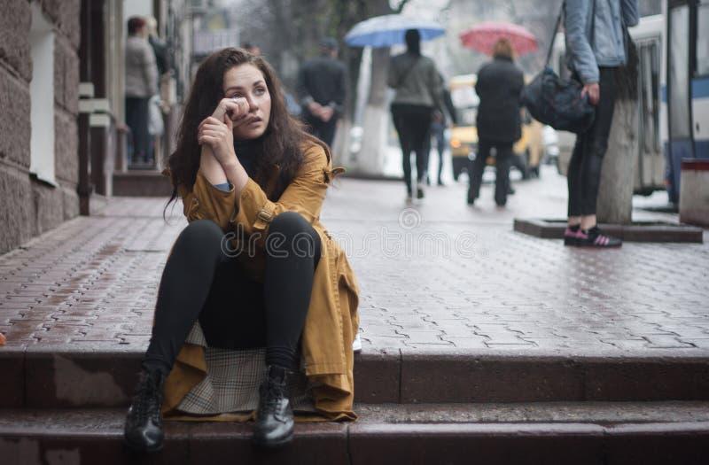 Молодые красивые выкрики женщины сидя в улице стоковая фотография