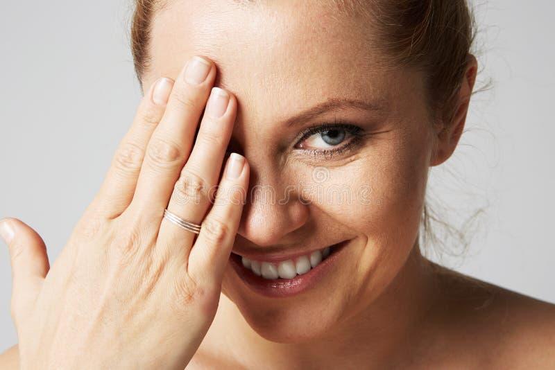 Молодые красивые женщины с белокурыми волосами исправленными позади, большими глазами, и нагими плечами усмехаясь и закрывают ее  стоковое изображение