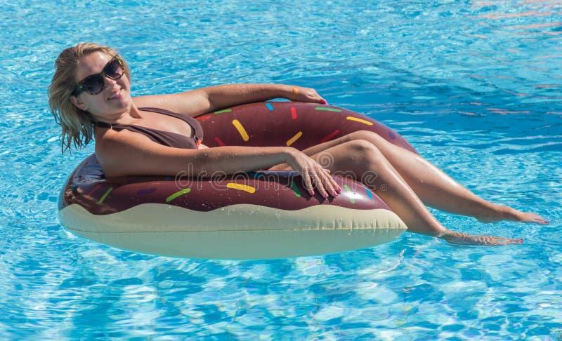 Молодые красивые заплывы девушки в бассейне стоковое изображение rf