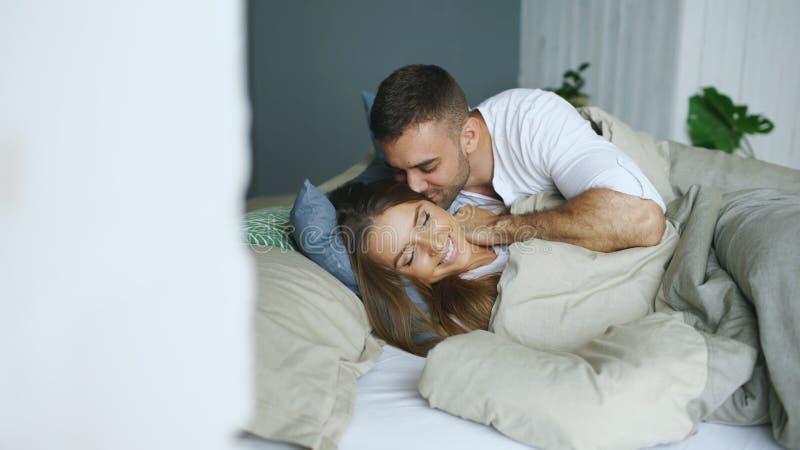 Молодые красивые и любящие пары просыпают вверх на утре Привлекательный поцелуй человека и обнимает его жену в кровати стоковая фотография