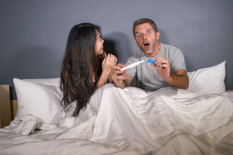 Молодые красивые и счастливые пары совместно в кровати смотря позитивный результат на тесте на беременность с sur беременной жены стоковые изображения