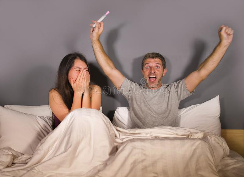 Молодые красивые и счастливые пары совместно в кровати смотря позитивный результат на тесте на беременность с sur беременной жены стоковые фото