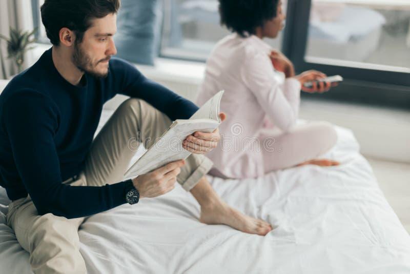 Молодые красивые межрасовые пары в кровати усилили с проблемами неверности стоковые изображения