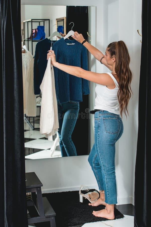 Молодые красивые покупки женщины, идя к примерочной в торговом центре моды, принимая решениее на чем купить, держащ 2 вешалки с стоковые изображения rf