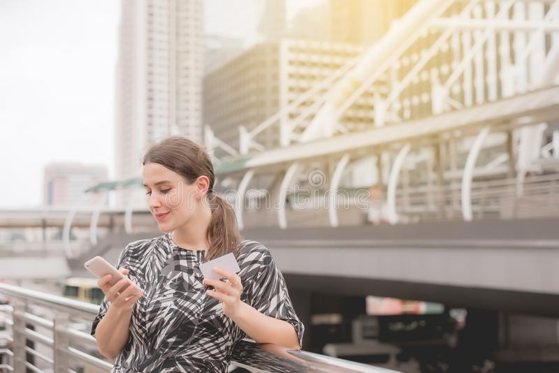 Молодые красивые покупки женщины онлайн с мобильным телефоном на разбивочном городе стоковые фотографии rf