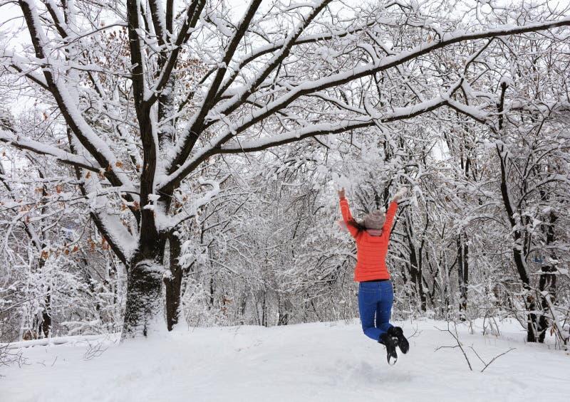 Молодые красивые прогулки и счастливо скачки девушки в зиме в покрытом снег лесе сказки около branchy постоянная старой стоковое изображение rf