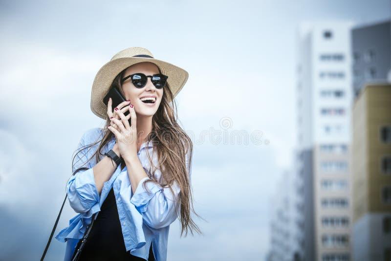 Молодые красивые рубашка и шляпа вычуры дамы модели женщины с mobi стоковая фотография rf