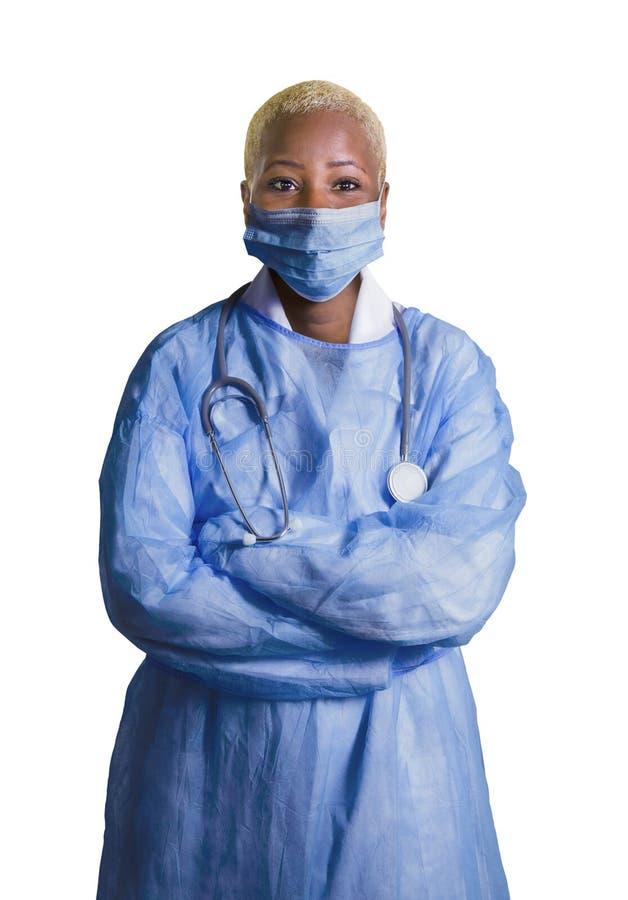 Молодые лицевой щиток гермошлема и синь привлекательного и уверенного черного Афро-американского доктора медицины нося scrubs сто стоковые изображения