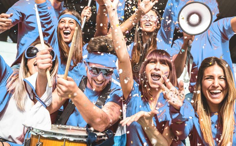 Молодые любительские сторонники футбольного болельщика веселя с флагами наблюдая местную спичку чашки футбола на стадионе - групп стоковые изображения