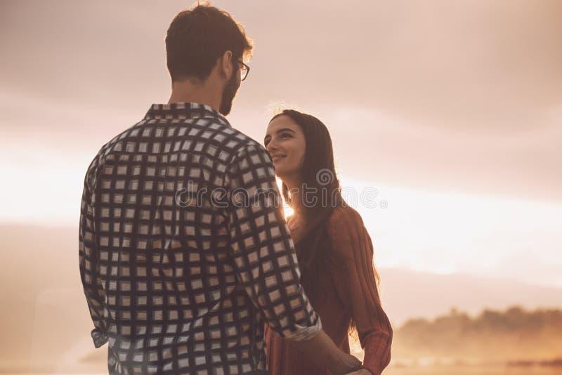 Молодые любящие пары держа руки на заходе солнца стоковые фото