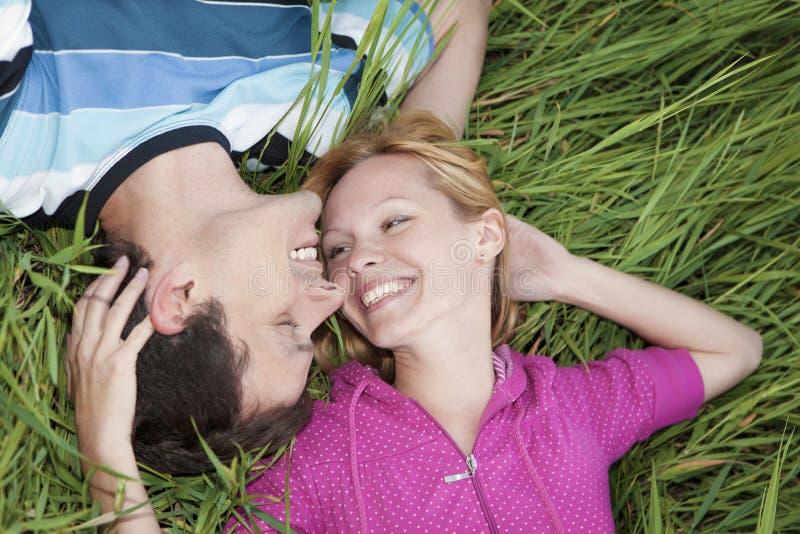 Молодые любящие пары лежа на зеленой траве стоковые фотографии rf