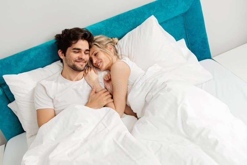 Молодые любящие пары лежа на кровати, наслаждаясь стоковое изображение