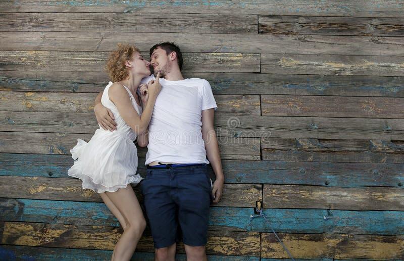 Молодые любящие пары наслаждаясь природой, молодым человеком и девушкой в белом платье лежат совместно стоковое фото rf