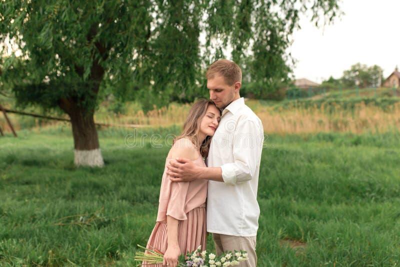 Молодые любящие пары обнимая и танцуя на зеленой траве на лужайке Красивые и счастливые женщина и человек нежно касаются одину др стоковые фотографии rf