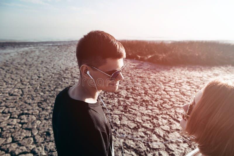 Молодые любящие пары подростков в солнечных очках держа руки дальше стоковое фото rf