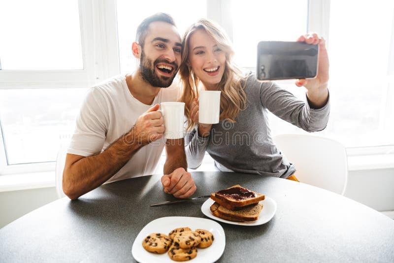 Молодые любящие пары сидя на кухне для того чтобы иметь завтрак принят стоковая фотография rf