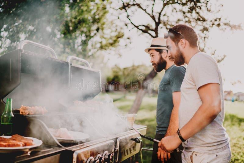 Молодые люди варя на барбекю, жарящ людей мяса и vegetablesYoung варя на барбекю, жарящ мясо и овощи стоковое изображение