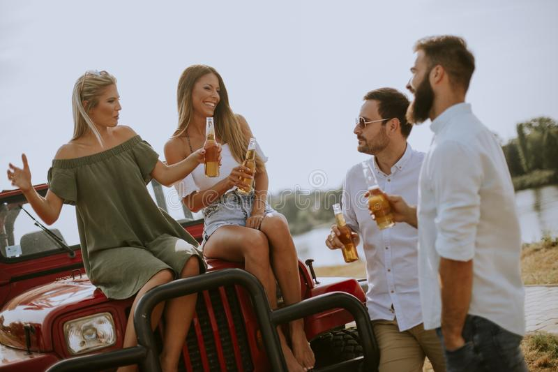 Молодые люди выпивая и имея потеху на автомобиле на открытом воздухе на горячем летнем дне стоковое фото rf