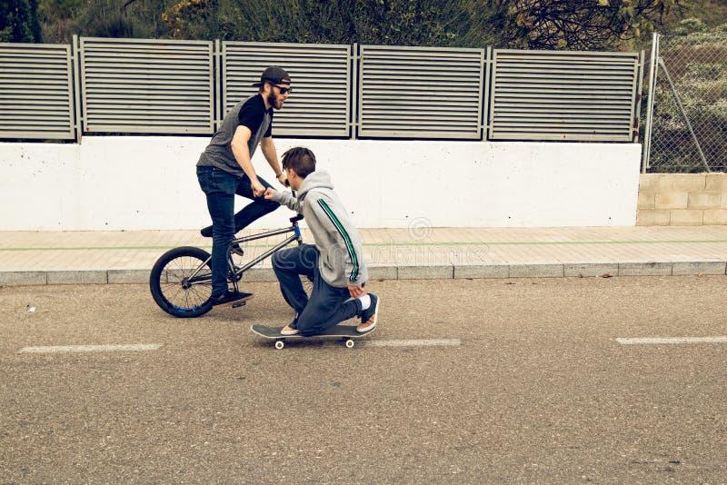 Молодые люди ехать велосипеды и скейтборды в городе Парни с коньком и bmx вниз по улице стоковое изображение rf