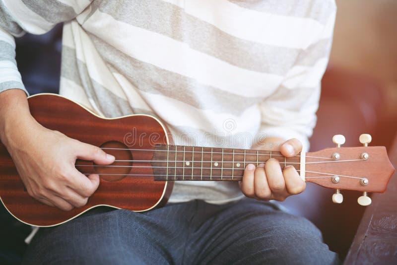 Молодые люди играют гитару для вентиляторов для того чтобы слушать в рестораны стоковое изображение
