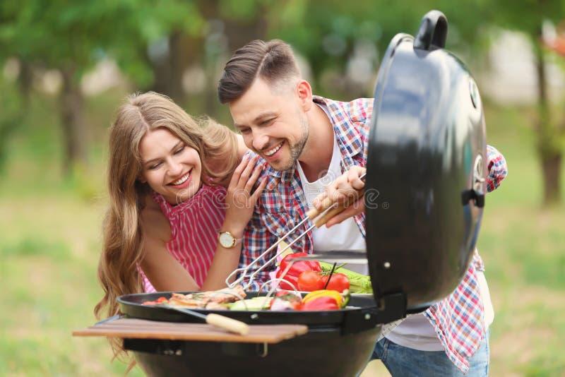 Молодые люди имея барбекю с современным грилем стоковое фото
