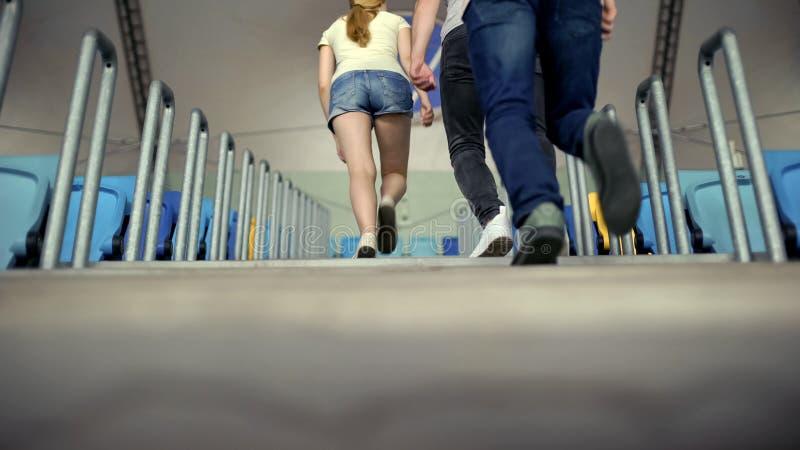 Молодые люди ища места на стойках, болельщики на гонках или футбольный матч стоковое фото rf