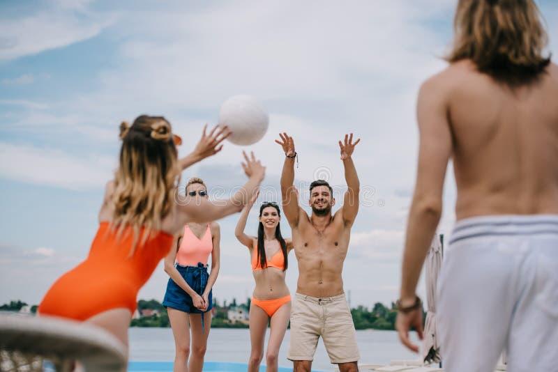 молодые люди и женщины играя волейбол совместно стоковая фотография rf