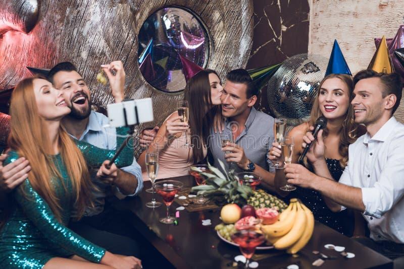 Молодые люди отдыхает в ультрамодном ночном клубе Парень в белой рубашке и девушка в черном платье поют стоковое фото