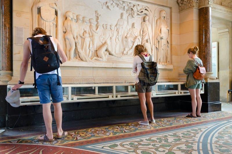 Молодые люди посещает экспозицию о истории церков Kaiser Wilhelm мемориальной в старой части виска, Берлина, Германии стоковое изображение