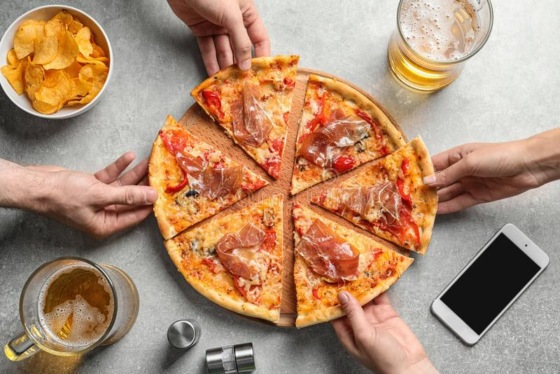 Молодые люди принимая куски вкусной пиццы с мясом стоковая фотография rf