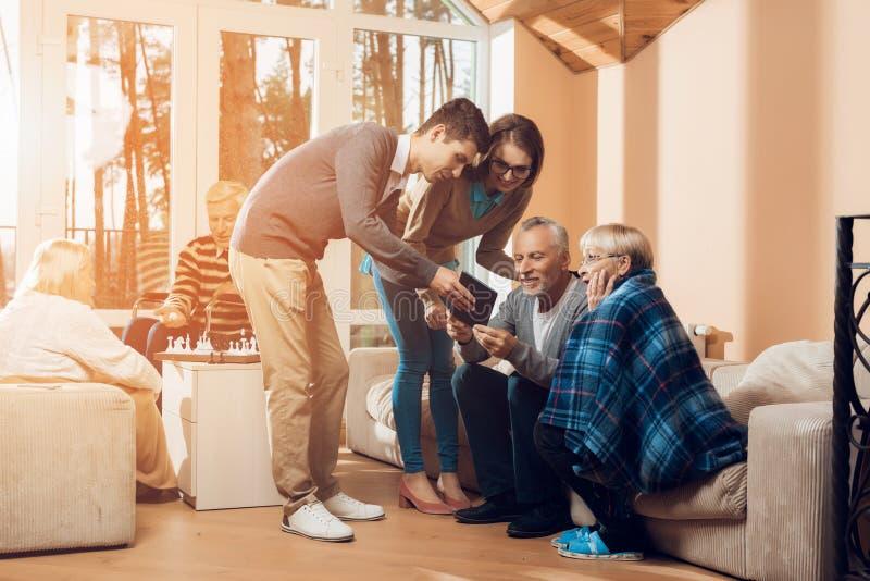 Молодые люди пришло навестить более старый человек и женщина в доме престарелых стоковые фото