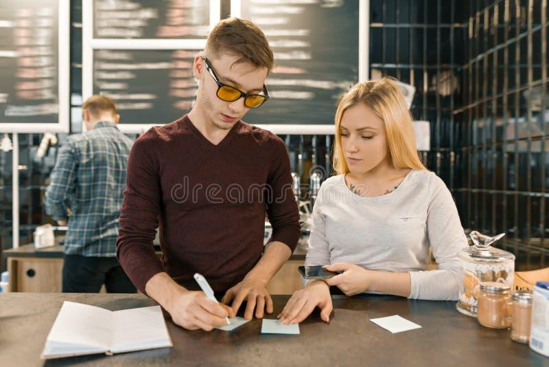Молодые люди работая в кофейне, человеке и женщине около счетчика бара, получая заказа по телефону, barista на предпосылке кофе стоковое фото