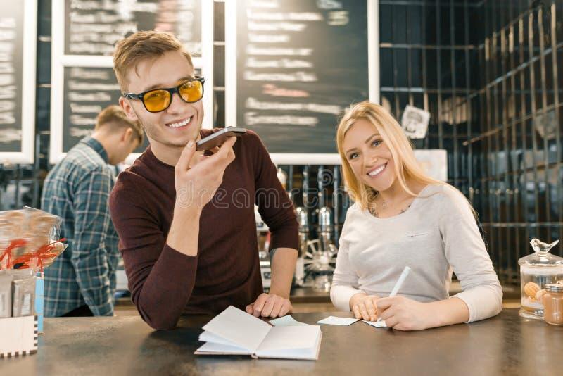 Молодые люди работая в кофейне, человеке и женщине около счетчика бара, получая заказа по телефону, barista на предпосылке кофе стоковые фотографии rf
